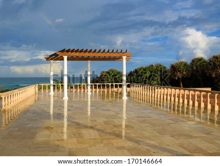 Inviting terrace and pergola overlooking the ocean - stock photo