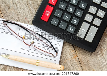Invoice with balance due, calculator,pen and glasses - stock photo