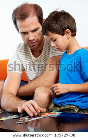 involved father helps son with puzzle - stock photo