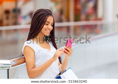 Involved in chatting . Petty vivacious smiling girl holding mobile phone and package while making shopping