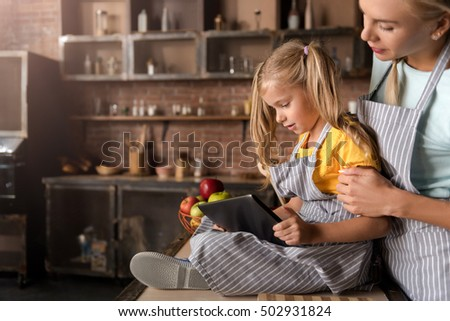 Involved little girl looking at the tablet with her mother