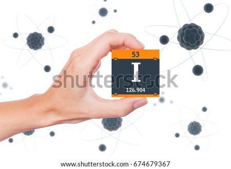 Iodine element symbol handheld and atoms floating in background