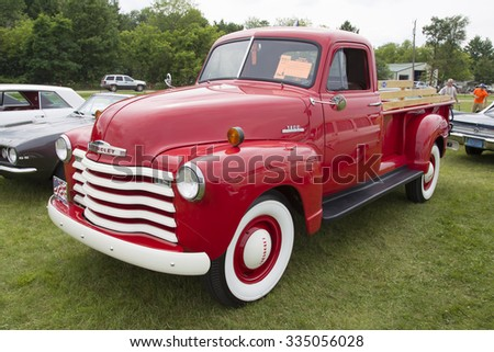 IOLA, WI - JULY 11:  Side of Red 1953 Chevrolet pickup truck at Iola 43nd Annual Car Show July 11, 2015 in Iola, Wisconsin. - stock photo