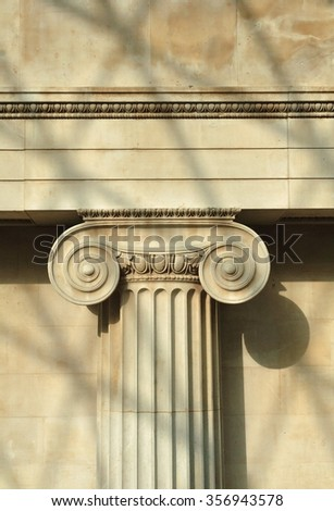Ionic capital with shadow of modern roof frame.