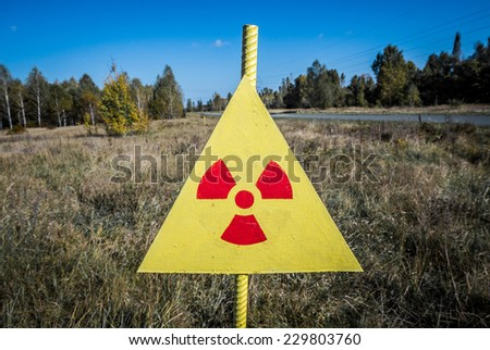 Ionizing Radiation sign next to Red Forest in Chernobyl Nuclear Power Plant Zone of Alienation, Ukraine - stock photo