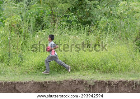 IQUITOS, PERU - CIRCA 2014: An unidentified boy run along the green forest circa 2014 in Iquitos, Peru.