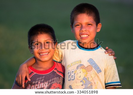 IQUITOS, PERU - CIRCA 2014: Two boys smile for the camera at the sunset light circa 2014. - stock photo