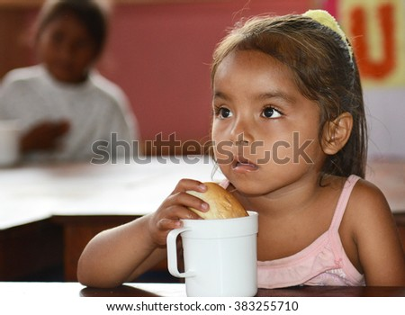 IQUITOS, PERU - OCTOBER 12, 2015: Snack time in the Santa Ana Village Kindergarten. A young girl has a roll and milk. - stock photo