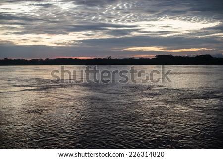 Iquitos, Peru: Sunrise in the Amazon river - stock photo