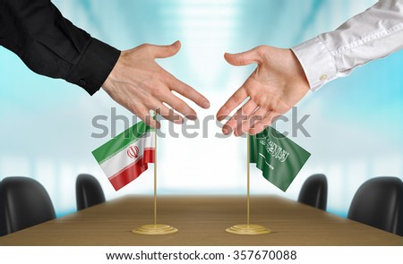 Iran and Saudi Arabia diplomats shaking hands to agree deal - stock photo