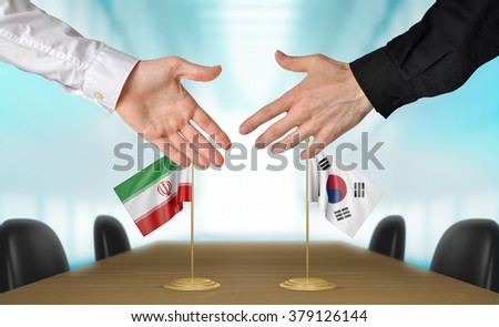 Iran and South Korea diplomats shaking hands to agree deal - stock photo