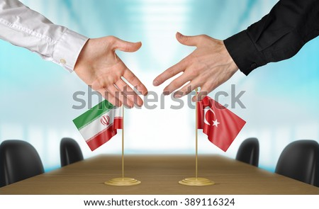 Iran and Turkey diplomats shaking hands to agree deal - stock photo