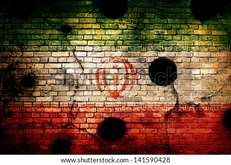 Iran flag on brick wall with bullet holes - stock photo