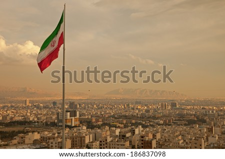 Iran flag waving  in the wind above skyline of Tehran lit by orange glow of sunset. - stock photo