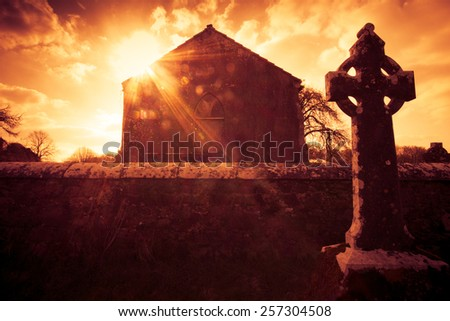 Ireland celtic cross at medieval church cemetery under fiery sky - stock photo