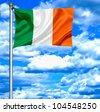 Ireland waving flag against blue sky - stock photo