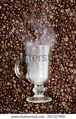 Irish coffee glass stuck in fresh coffee beans. Smoke is coming out of the glass. - stock photo