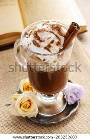 Irish coffee, open book in the background - stock photo