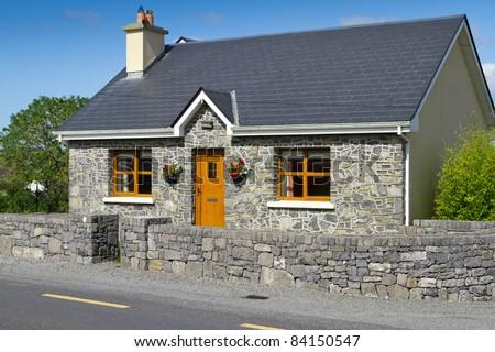 Irish cottage house with stone front - stock photo