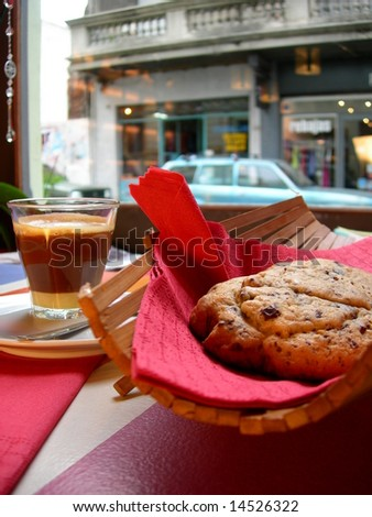 Irish cream coffee with huge cookie in a city cafe place - stock photo