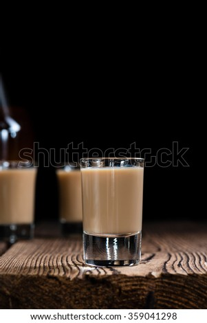 Irish Cream Liqueur (detailed close-up shot) on wooden background - stock photo