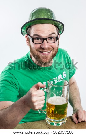 Irish guy in bar red hair glasses green clothes hat toasting to Eire on Saint Patty's day cute young - stock photo