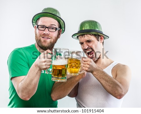 Irish men friends toasting to St. Patrick in green hats on holiday with large glasses of beer at bar, mustache, shirt, and shouting - stock photo