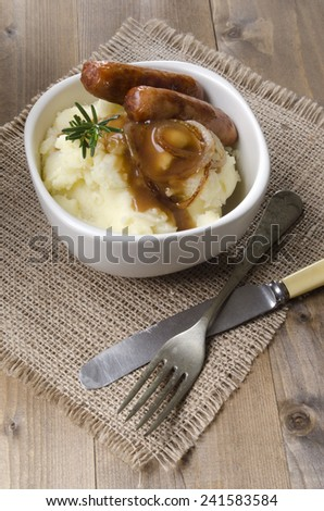 irish sausage, mashed potato and rosemary with onion gravy in a bowl on jute - stock photo