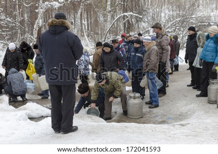 IRKUTSK, RUSSIA - JAN 19: People take water in the Holy well spring on Epiphany-day in January, 19 2012 in Irkutsk region.