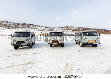 IRKUTSK, SIBERIA, RUSSIA - FEB 21, 2017 : Group of Wazik UAZ-452, the 4WD Russian Minibus waiting for passengers on the ice road of the frozen Lake Baikal in winter.