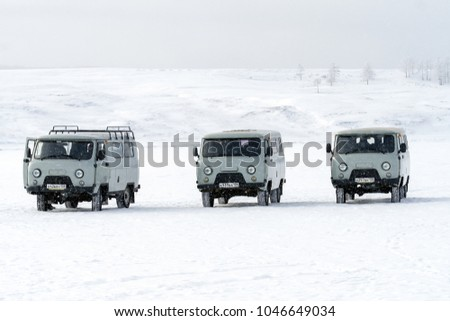 IRKUTSK, SIBERIA, RUSSIA - MAR 10, 2018 : Group of Wazik UAZ-452, the 4WD Russian Minibus waiting for passengers on the ice road of the frozen Lake Baikal with snowfall in winter.