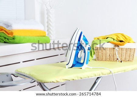 Iron and clothes on ironing board on interior background - stock photo