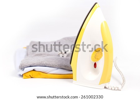 Iron and pile of clothes on a white background. - stock photo