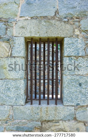 Iron bars close off the wall of an old jail cell window. - stock photo