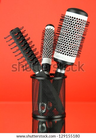Iron basket with round hair brushes, on color background