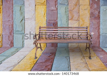 Iron bench at stone wall and floor corner. - stock photo