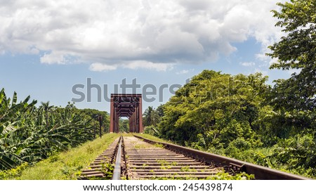 Iron bridge in a railroad set in a tropical country featuring beautiful cloudscape and exhuberant vegetation - stock photo