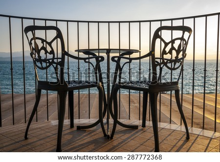 Iron chairs and table in wooden terrace lake view - stock photo