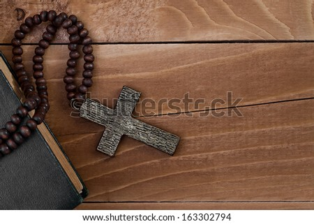 Iron cross with a book on a wooden surface - stock photo