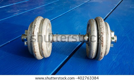Iron dumbbell on a blue wooden deck. - stock photo
