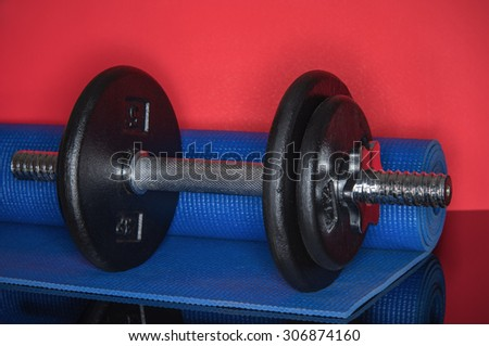 Iron dumbell on red background with roll mat - stock photo