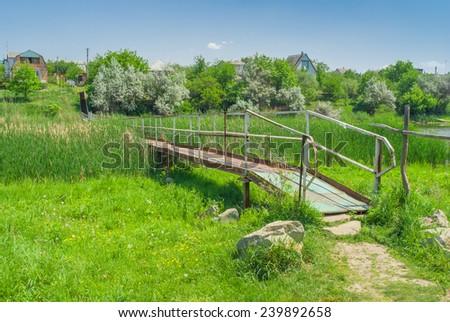 Iron footbridge over small Ukrainian river Sura - stock photo