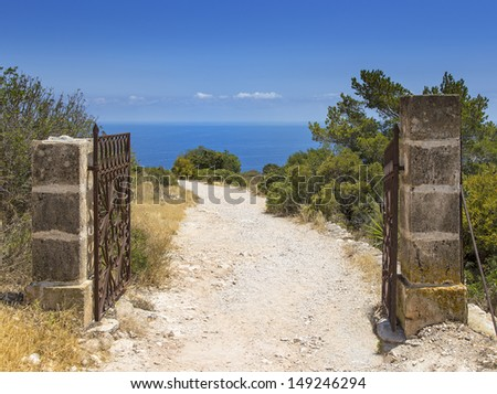 iron gate entrance of a private garden with view over pine trees and blue ocean - stock photo