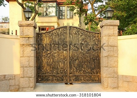 Iron gate with yellow wall and stone columns. - stock photo