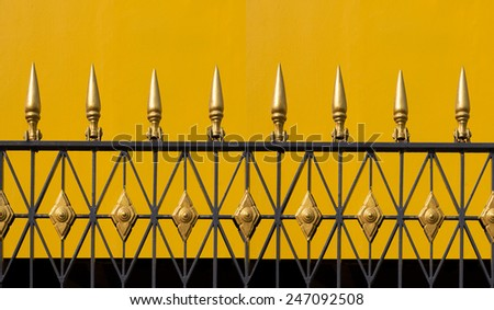 Iron golden fence.Background is yellow cement wall.Pattern upper are sharp spear shape. - stock photo