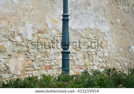 Iron lamppost dividing the old wall in the park. The focus is on the lamppost.  /  Iron lamppost