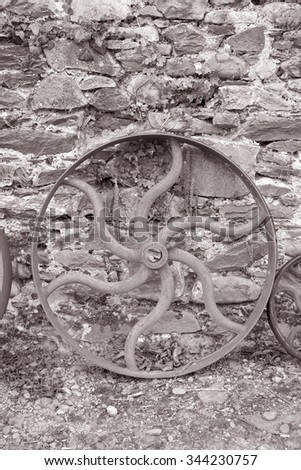 Iron Mill Wheel on Stone Wall in Black and White Sepia Tone