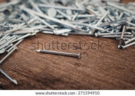 iron nails on wooden background - stock photo