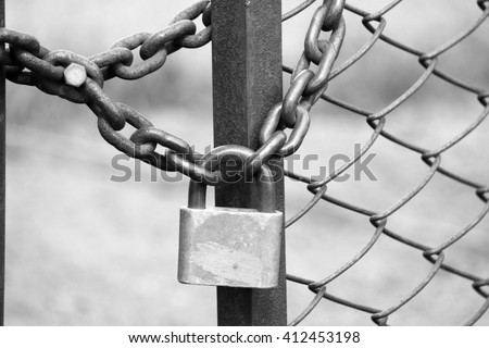 iron padlock on iron fence with a chain-link fencing, black and white photo - stock photo