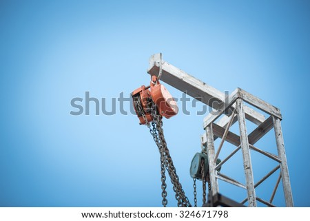 iron pulley on blue sky - stock photo